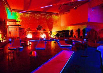 Ein Indoor Schwarzlicht Blacklight Minigolf Platz mit Themenausstattung