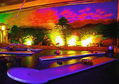 Effektvolle Blacklight Minigolf Anlage in einer Indoor Halle, mit vielen Lichteffekten und dekorativen Objekten - ein großes Abenteuer für große und kleine Menschen